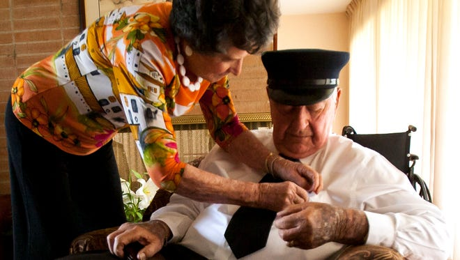 Nellie Bootz (left) adjusts the badge on Charlie Bootz' shirt at their home in Glendale, Arizona. The two have been married for 66 years.