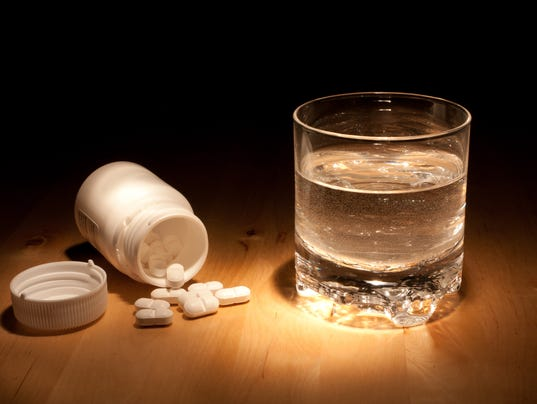 A glass of water stood next to a jar of pills