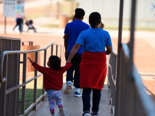 Una madre y su hija caminan hacia el patio en el Centro Residencial Familiar del Sur de Texas, en Dilley, Texas.