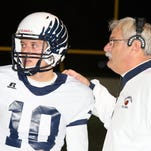 Senior quarterback Kyle Collins gets the play from Farmington head coach John Bechtel.