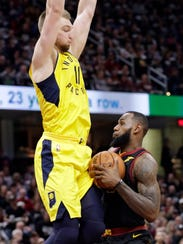 Cleveland Cavaliers' LeBron James, right, is stopped