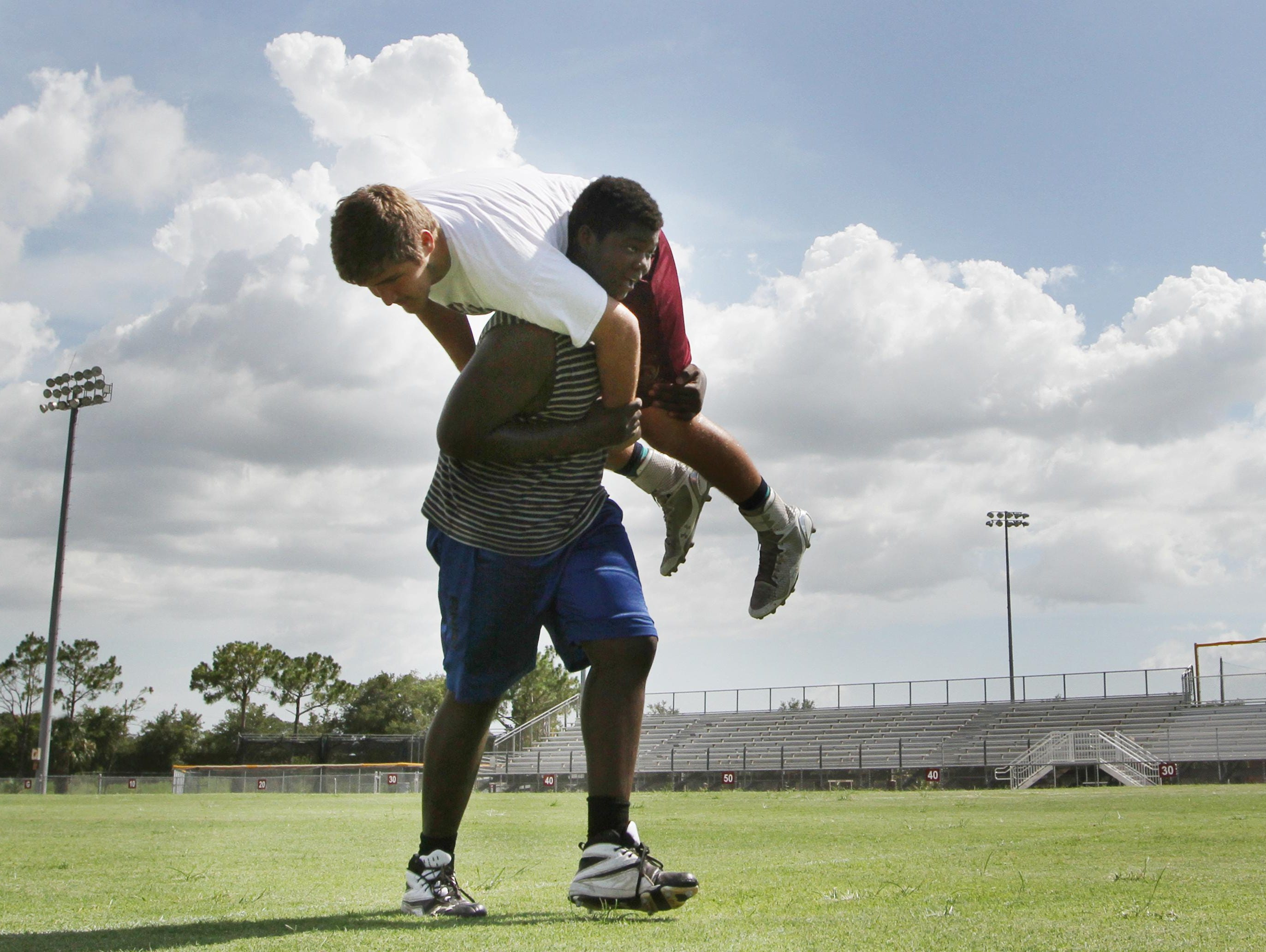 Riverdale tackle Finely Felix and Cole Schneider work on strength and agility during summer practice last week.
