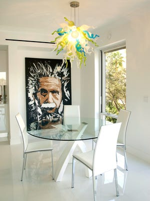 """The dining area of the Kosch home exemplifies its modern style. Artist Michael Israel's """"Einstein"""" oil on canvas and a blown glass chandelier add color and whimsy to their glacial-white surroundings."""