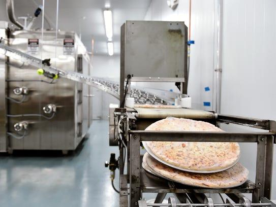 Flash-frozen pizzas come off the conveyer belt out