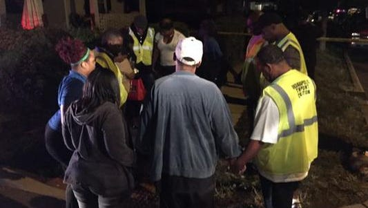 Members of the Ten Point Coalition pray with family members of victims at the scene of a quadruple shooting on the Northside that left a child dead on Sept. 19, 2015.