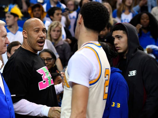 """FILE - In this March 4, 2017, file photo, UCLA guard Lonzo Ball, right, shakes hands with his father LaVar following an NCAA college basketball game against Washington State in Los Angeles. UCLA won 77-68. LaVar Ball told Southern California News Group for a story published online on April 6, 2017, that UCLA was eliminated in the NCAA tournament because """"three white guys"""" couldn't pick up the slack after his son suffered a hamstring injury. (AP Photo/Mark J. Terrill, File)"""