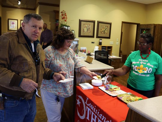A pair of travelers from Idaho are greeted at the Downtown Shreveport Visitors' Center with a slice of king cake on Feb. 14. The Tourist Bureau welcomed visitors with free king cake on Feb. 14 and Feb. 21.