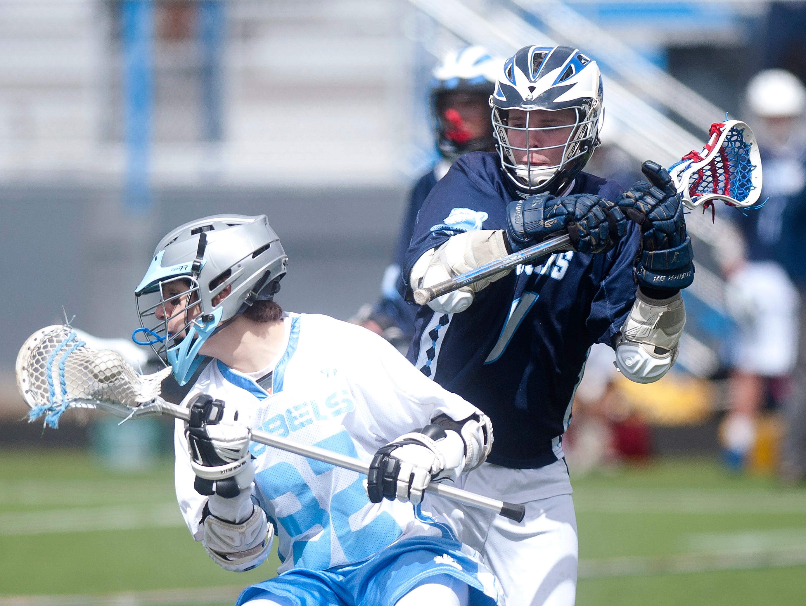 Mount Mansfield's Travis Benson, right, looks to knock the ball away from South Burlington's Max Capano during Saturday's boys lacrosse game in South Burlington.