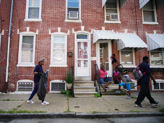 Participants in the Wilmington Police Department Youth Academy walks past residents along the 900 block of Kirkwood Street while doing a community cleanup with police officers.
