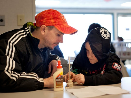 Jason Johnson, of Burtchville Township, helps his son, Tristan Wilbanks, 7, glue together a model boat Saturday at the Great Lakes Maritime Center in Port Huron.