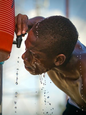 West Los Angeles College cross-country runner Tawuan Cargill dumps water over his head after running amid high temperatures at Kenneth Hahn State Recreation Area in Los Angeles Tuesday, Sept. 16, 2014. (AP Photo/Los Angeles Times, Allen J. Schaben)