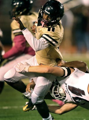 Whitehaven senior RB Kylan Watkins fights through a tackle by Collierville senior MLB Tylet Garvey in the first quarter Friday.