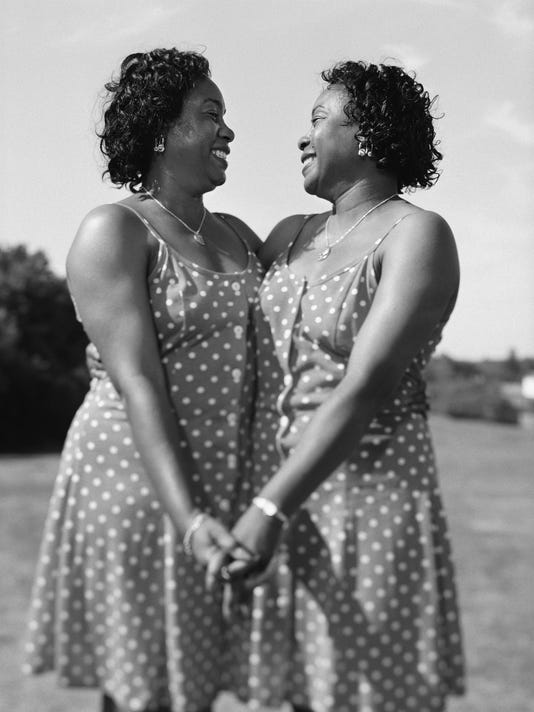 Portrait of women twins holding hands