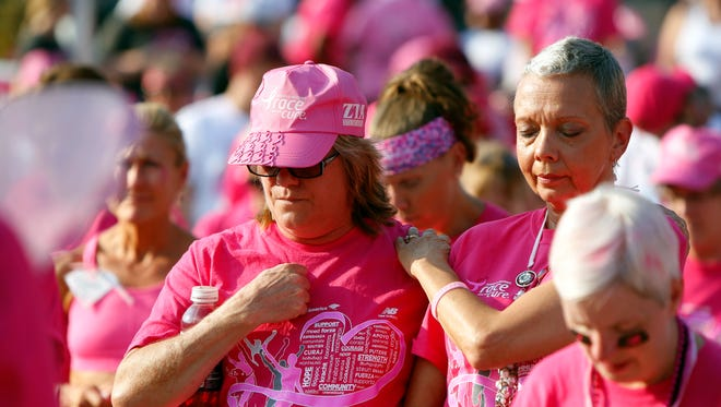 Sylvia Breier, left, and Sandy Howard embrace Saturday during the celebration of hop at the Susan G. Koman Race for a Cure event Downtown on the riverfront. Both women are cancer survivors, though Howard has recently had to undergo more chemotherapy treatments.