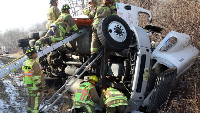 Brewster firefighters work to remove an injured truck driver from the cab of his tractor-trailer after it rolled over on the ramp from northbound Interstate 684 to eastbound Interstate 84 in the town of Southeast Jan. 16, 2015. The driver and his passenger were transported to Danbury Hospital with non-life threatening injuries.