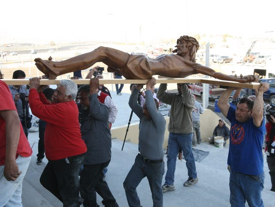 Workers install the wooden cross at the altar at the
