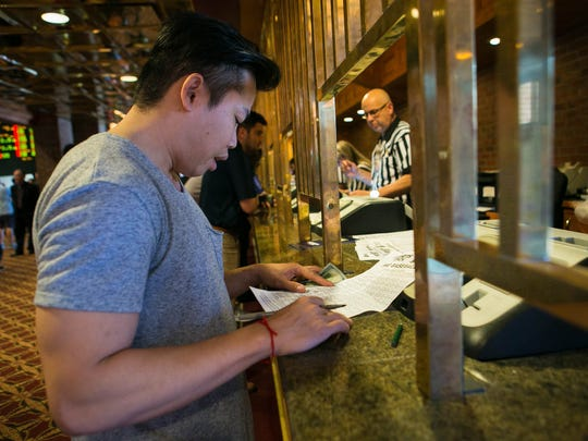 Ivan Dinh of Wilmington places a bet on June 5 at the Casino at Delaware Park in Stanton. Since single-sport wagering was legalized in the First State, Delaware's three casinos, after money was allocated to the state and to their respective racetracks,netted almost $5.2 million.