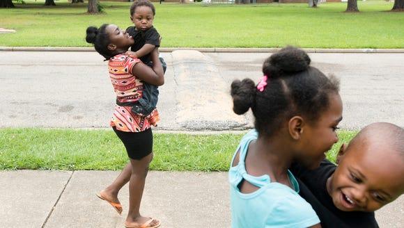 Temeisha Thomas, 9,  left, holds Junior Smith, 1, as