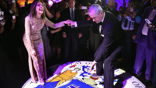 New Jersey's 56th governor, Phil Murphy, and first lady Tammy Murphy stop during their first dance while the governor points to the state seal of New Jersey projected on the floor at MetLife Stadium in East Rutherford on Jan. 16, 2018. The event was the culmination of a five-day celebration of Murphy's inauguration.