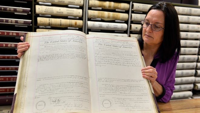 Stearns County Recorder Diane Grundhoefer shows a book of bounty patents granting land to civil war soldiers in documents originally signed by Abraham Lincoln in the recorder's office Tuesday, Oct. 14 in St. Cloud. The county is working to start digitizing all of its old books of records and expects to have them done by the end of 2015.