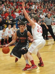 Austin Wurm drives toward the basket during their district