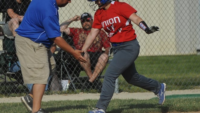 Union County coach Scott Gray congratulates Emma Adams as she rounds third base on her two-run home run against during Knightstown during the sectional championship game Wednesday, May 25, 2016.