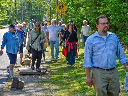 Residents and planners walk along Laker Lane as they tour and discuss plans for a village near Malletts Bay in Colchester, last week.