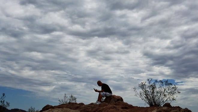 Mathew Kirkpatrick, of Phoenix, enjoys a cloudy morning on a hill at Papago Park in Phoenix. Up to one-quarter of an inch of rain is forecast Tuesday in south-central Arizona and up to one-half an inch is forecast in southwest Arizona, according to the National Weather Service.