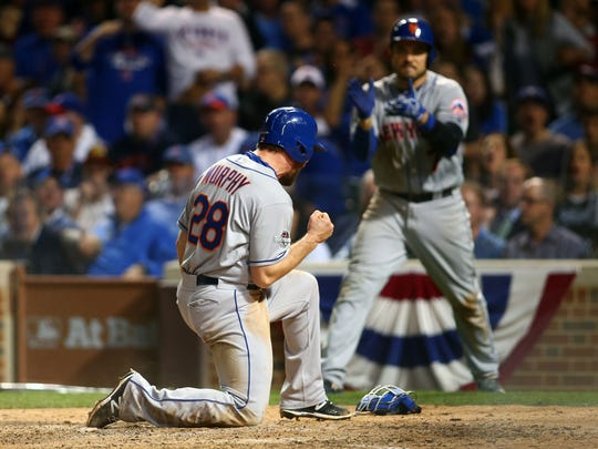 New York Mets second baseman Daniel Murphy (28) reacts after scoring a run in the seventh inning against the Chicago Cubs in game three of the NLCS at Wrigley Field.
