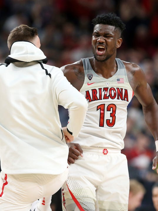 Arizona's Deandre Ayton, right, celebrates an overtime win with a teammate following the team's NCAA college basketball game against UCLA in the semifinals of the Pac-12 men's tournament Friday, March 9, 2018, in Las Vegas. Arizona won 78-67. (AP Photo/Isaac Brekken)