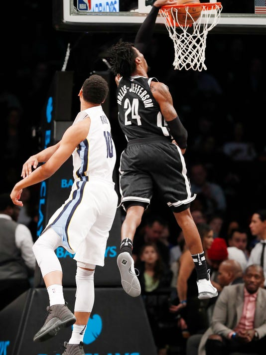 Memphis Grizzlies forward Ivan Rabb (10) watches as Brooklyn Nets forward Rondae Hollis-Jefferson (24) dunks during the first half of an NBA basketball game, Monday, March 19, 2018, in New York. (AP Photo/Kathy Willens)