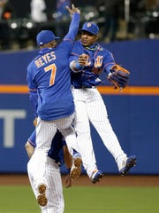 Mets' Jose Reyes (7) and Yoenis Cespedes (facing) celebrate after a game against the Atlanta Braves on Thursday, April 6, 2017, in New York. The Mets won 6-2.
