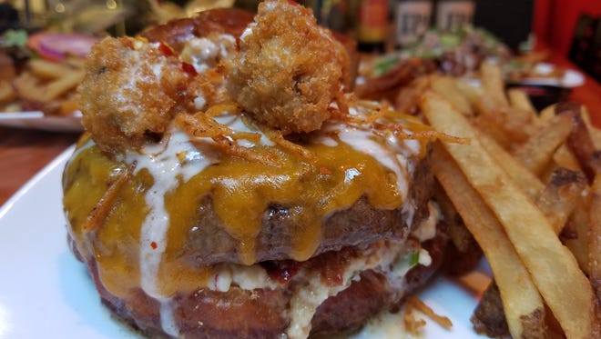 Kuma's, a 2016 Indy Burger Battle competitor, is known for its over-the-top burgers like the Gojira it featured in June. It sported garlic parmesan white wine sauce, cilantro red pepper vinaigrette, red pepper scallion mashed potatoes, bacon bits, cheddar, fried potato strings and bacon/sriracha/jalapeno/cream cheese stuffed fried mushrooms on top. Whew!