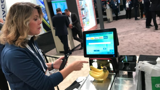 Laura Martin of NCR demonstrates a self-checkout scanner with a camera that can quickly identify produce and other items.