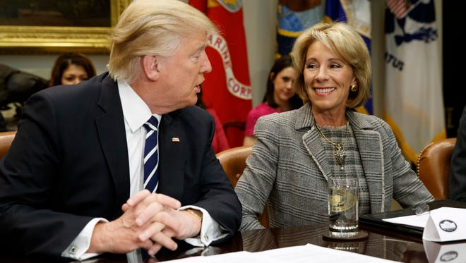 President Donald Trump looks at Education Secretary Betsy DeVos as he speaks during a meeting with parents and teachers, Tuesday, Feb. 14, 2017, in the Roosevelt Room of the White House in Washington.