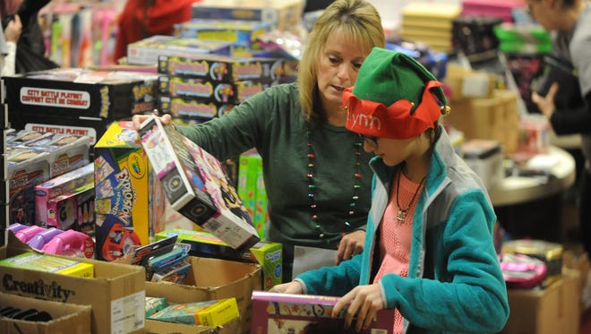 Ginger Martin and granddaughter Jazlynn Short select gifts for children Saturday during the Toys for Tots program.