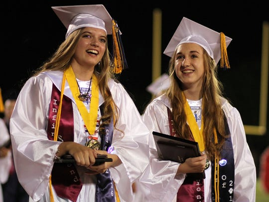 Valedictorians Katelyn Goodman, left, and Kelsey Smith look out into the audience for loved ones during the final walk of the senior class of 2016.