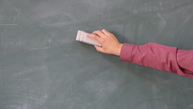 Teacher in the classroom board cleaning.
