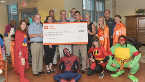 Direct Energy employees and state legislatures donate a check for $10,000 to the Ronald McDonald House of Delaware.