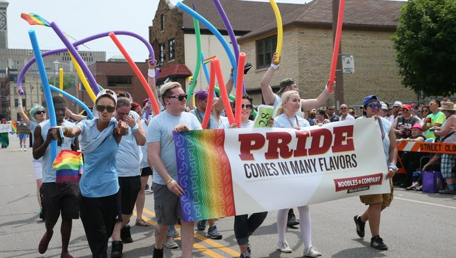 A group of men and women holding various colors of noodles and a sign promoting diversity at Noodles Company during the  2017 Milwaukee Pride Parade as it makes it's way north along S. 2nd St. in Milwaukee.