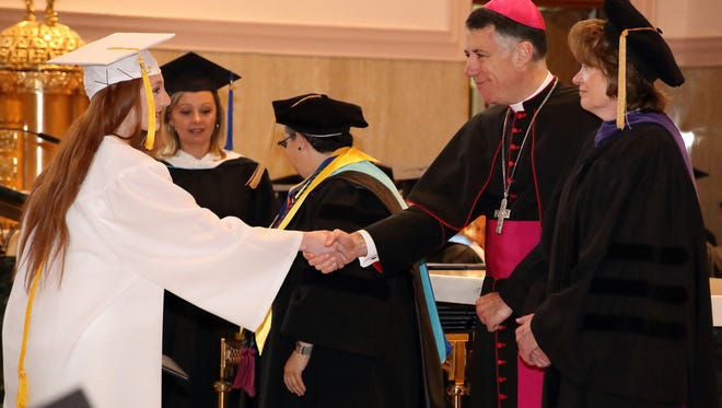 Bishop James F. Checchio awards a diploma to a member of the Mount Saint Mary Academy Class of 2017 during the June 3 commencement exercises.