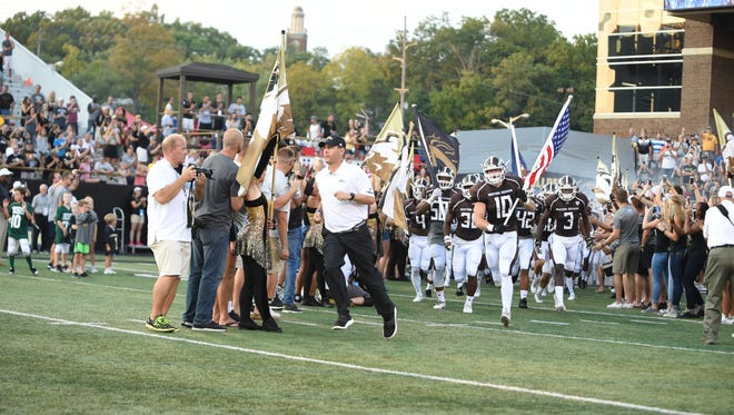 Western Michigan football coach Tim Lester leads his team out on the field. Lester played in the XFL for the Chicago Enforcers in 2001.