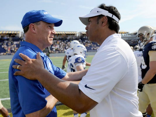 FILE - In this Oct. 5, 2013, file photo, Navy head coach Ken Niumatalolo, right, meets with Air Force head coach Troy Calhoun, left, after an NCAA football game in Annapolis, Md. This week doesn't feature too many intriguing matchups involving unranked teams, but the 50th meeting between these two service academies bears watching. Navy will attempt to remain undefeated while gaining some revenge after losing 28-14 to Air Force last season.  (AP Photo/Nick Wass, File)