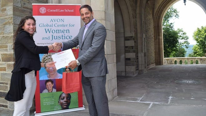 Cornell Law School Dean Eduardo M. Peñalver presents Olivia Colón with her certificate as a human rights lawyer for a day.