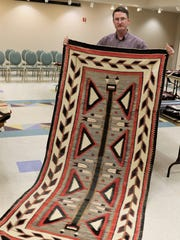 Farmington Museum Director Bart Wilsey displays a Teec Nos Pos-style rug that will be featured in Saturday's annual Navajo Rug Benefit Auction at the Farmington Museum at Gateway Park.