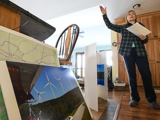 Christine Lang and her husband Dustin Lang, not pictured, are opposed to having seven nearly-500 foot high wind turbines built on a hill behind their home in Swanton.  She is seen with an illustration of what project opponents say the towers will look like from their neighborhood.