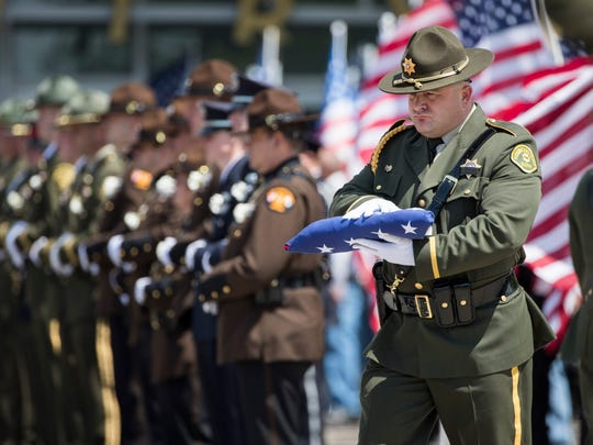 A member of the Pottawattamie County Sheriff's Office presents a folded flag to the family of Pottawattamie County sheriff's deputy, Mark Burbridge, after the funeral ceremony at the Mid-America Center in Council Bluffs, Iowa on Monday, May 8, 2017. Mark Burbridge, 43, was fatally wounded Monday, May 1, 2017 when a prisoner he and another deputy were transporting got hold of a gun and opened fire, officials said. BRENDAN SULLIVAN/THE WORLD-HERALD