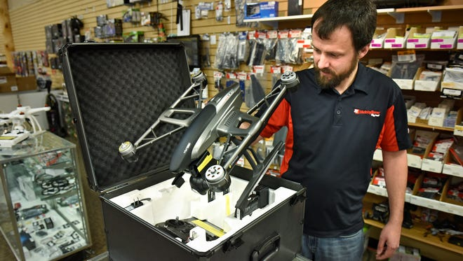 Baker's HobbyTown manager Jason Wester unpacks a drone Tuesday at the Waite Park store. A registration system for all drones has been proposed by the Department of Transportation.