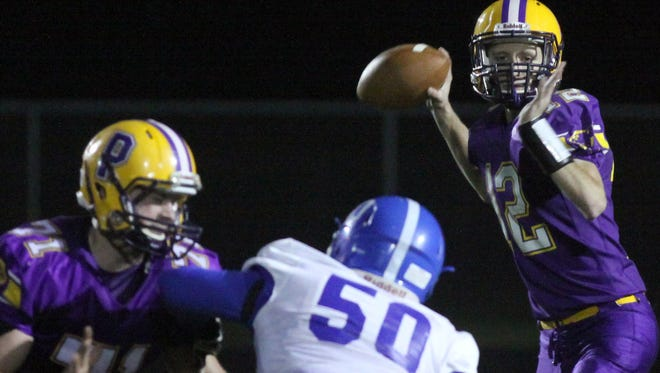 Pitttsville quarterback Luke Denniston looks downfield for a receiver during the first half of Friday's WIAA Division 7 playoff matchup with Assumption.