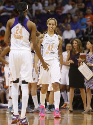 Mercury's Brittney Griner comes out to high-five teammate DeWanna Bonner after a double-technical on Lynx head coach Cheryl Reeve at US Airways Center in Phoenix, AZ on August 23, 2015.